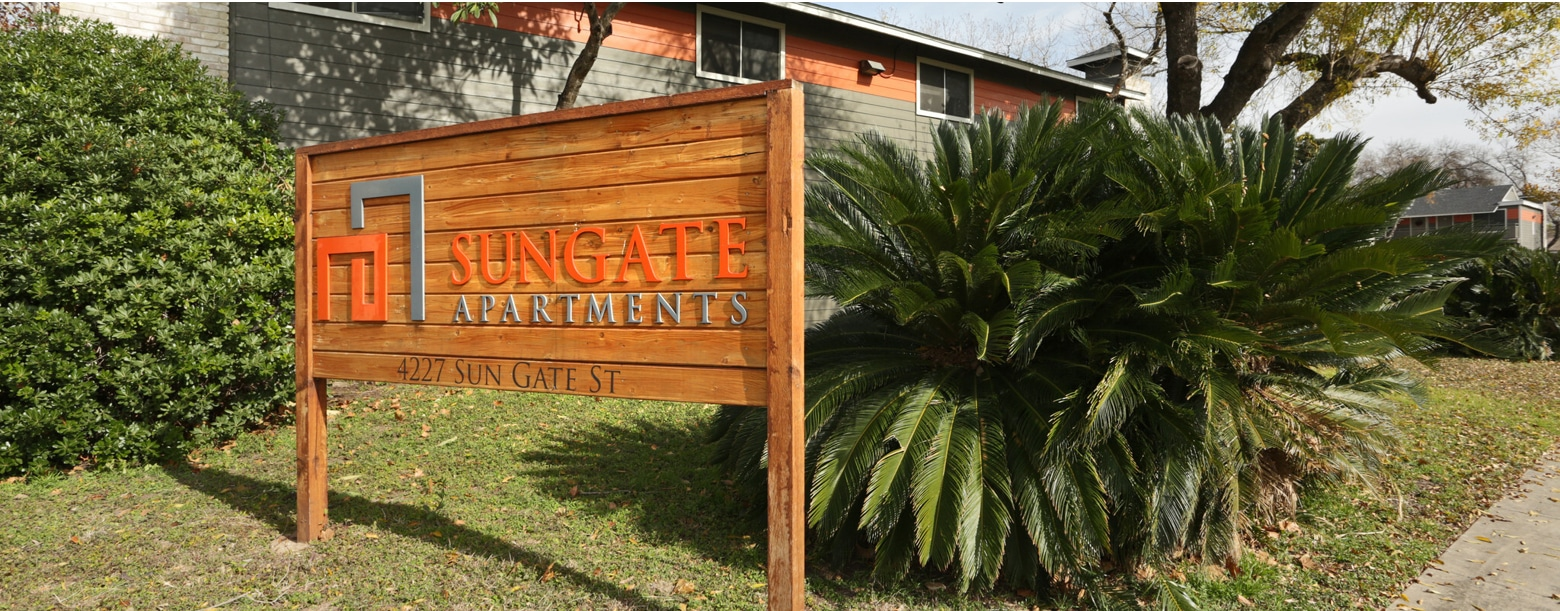Signage of Sungate Apartments in San Antonio, TX with buildings in the back.